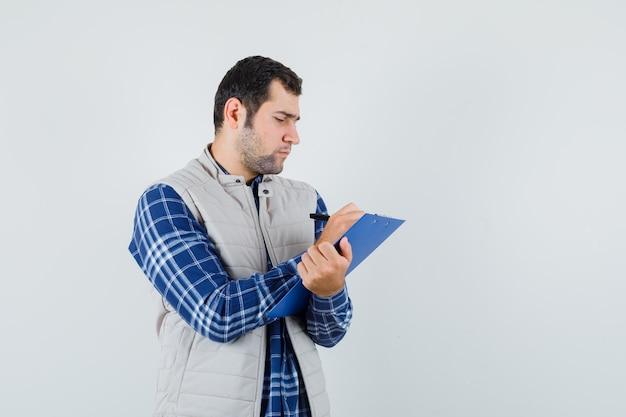 Jeune homme en chemise, veste notant quelque chose sur papier et à la recherche de concentré