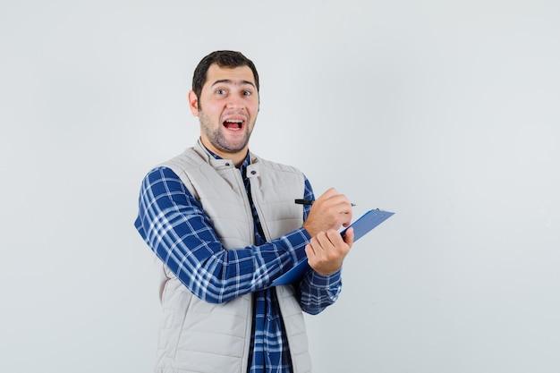 Jeune homme en chemise, veste notant quelque chose et à la satisfaction