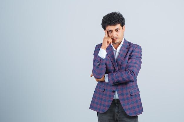 Jeune homme en chemise, veste, pantalon debout dans une pose de réflexion et l'air sensé, vue de face.