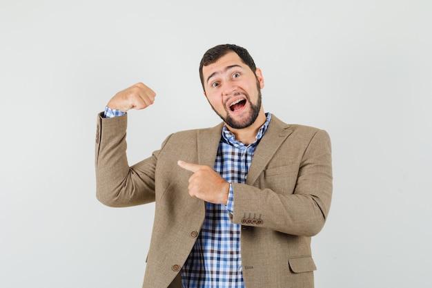 Jeune homme en chemise, veste pointant sur ses muscles et à la fierté, vue de face.