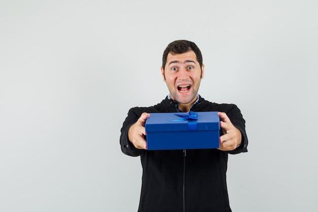 Jeune homme en chemise, veste présentant une boîte-cadeau et à la joyeuse