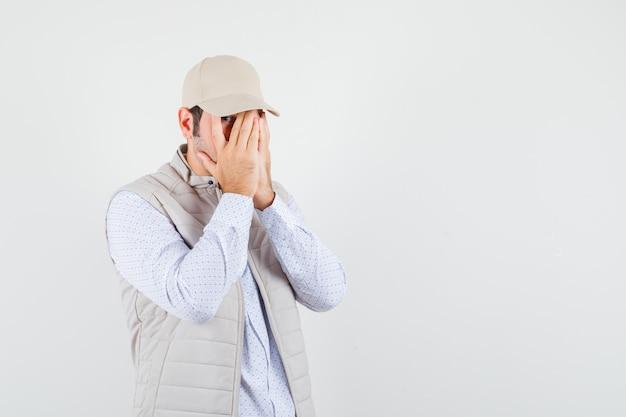Jeune homme en chemise, veste sans manches, casquette couvrant le visage avec les mains tout en regardant à travers les doigts et à la timide, vue de face. espace pour le texte