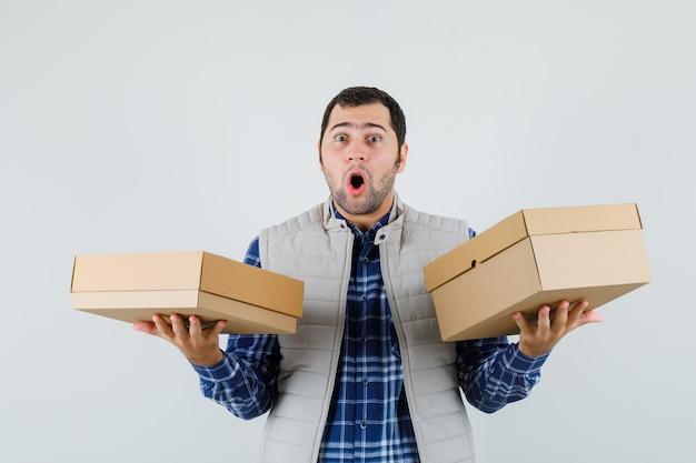 Jeune homme en chemise, veste soulevant des boîtes et à la surprise, vue de face.