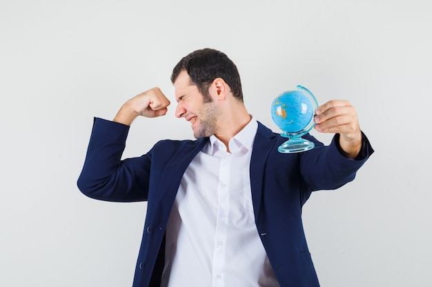 Jeune homme en chemise et veste tenant le globe de l'école et à la béatitude