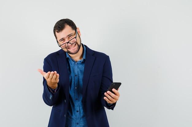 Jeune homme en chemise, veste tenant le téléphone portable et souriant, vue de face.