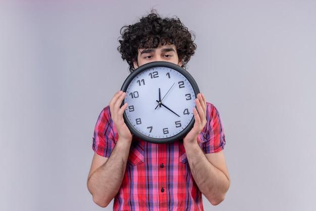 Jeune homme cheveux bouclés chemise colorée isolée se cachant derrière l'horloge