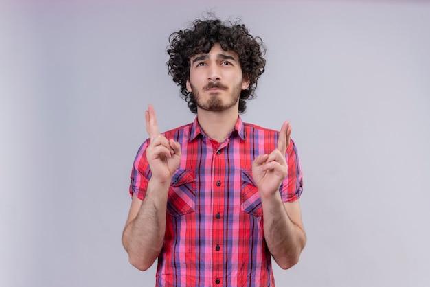 Jeune homme cheveux bouclés isolé chemise colorée croiser les doigts en espérant