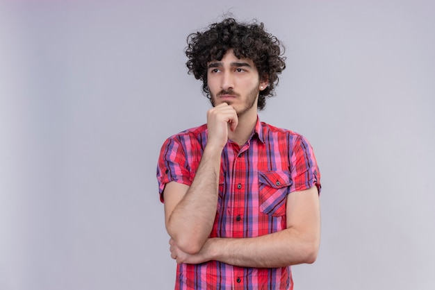Jeune homme cheveux bouclés isolé chemise colorée pensée