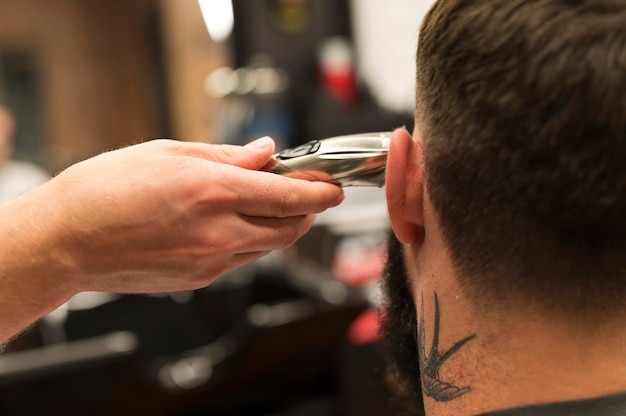 Jeune homme chez le coiffeur se faisant couper les cheveux