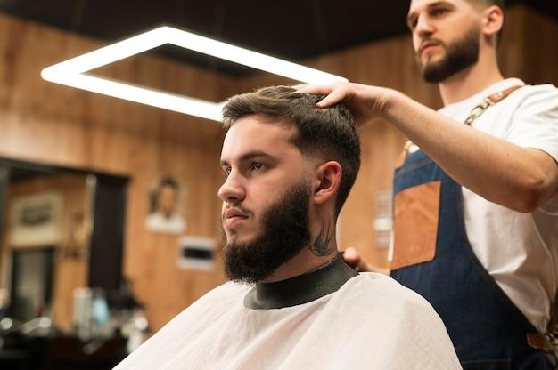 Jeune homme chez le coiffeur vérifiant la nouvelle coupe de cheveux