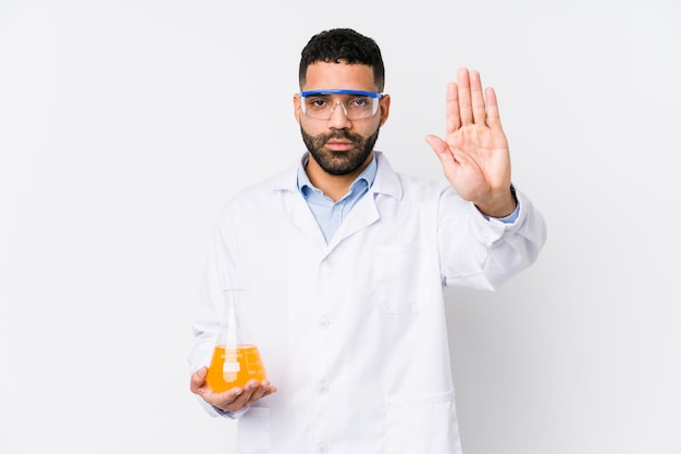 Jeune homme chimique arabe isolé debout avec la main tendue montrant le panneau d'arrêt, vous empêchant.