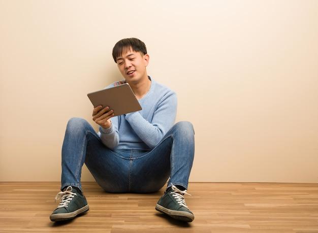 Jeune homme chinois assis à l'aide de sa tablette faisant un geste romantique