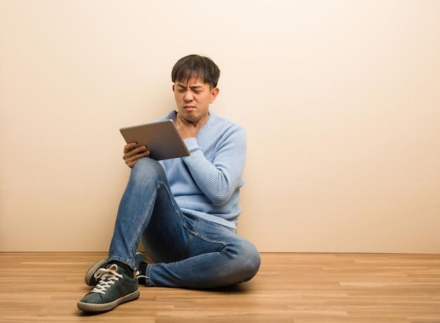 Jeune homme chinois assis en utilisant sa tablette toussant, malade en raison d'un virus ou d'une infection