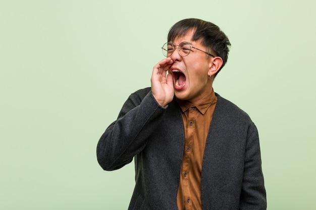 Jeune homme chinois contre un mur végétal