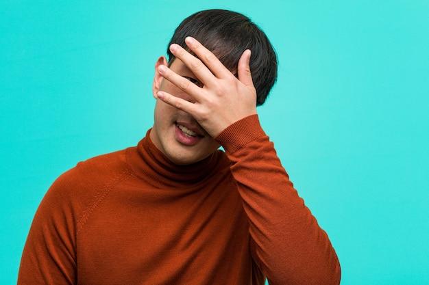 Jeune homme chinois embarrassé et riant en même temps