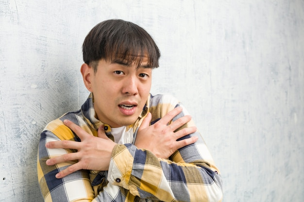 Jeune homme chinois face closeup va froid en raison de la basse température
