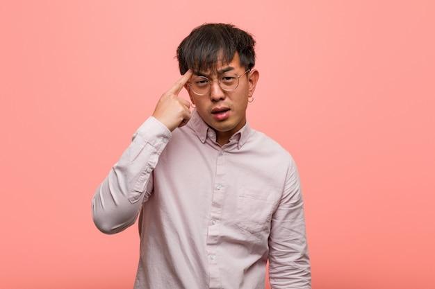 Jeune homme chinois faisant un geste de déception avec le doigt