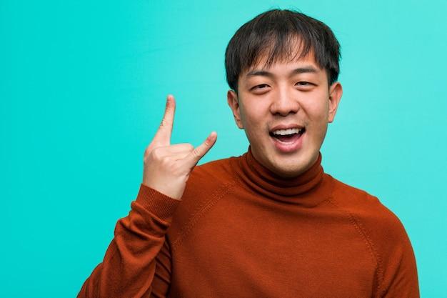 Jeune homme chinois faisant un geste rock