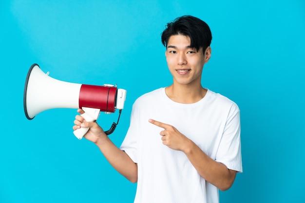 Jeune homme chinois isolé sur fond bleu tenant un mégaphone et côté pointant