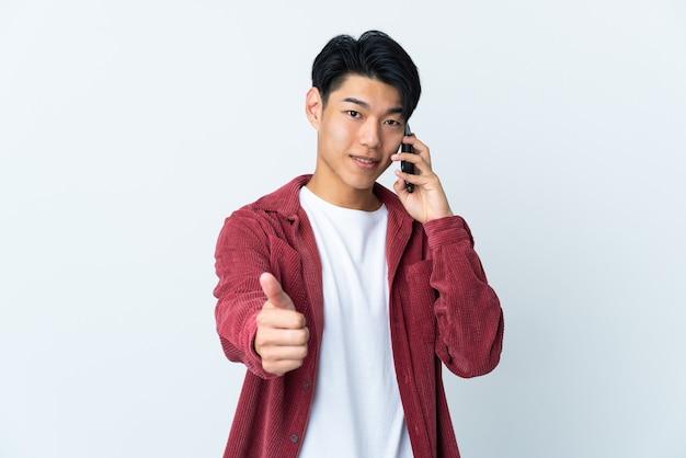 Jeune homme chinois isolé sur un mur blanc en gardant une conversation avec le mobile tout en faisant les pouces vers le haut