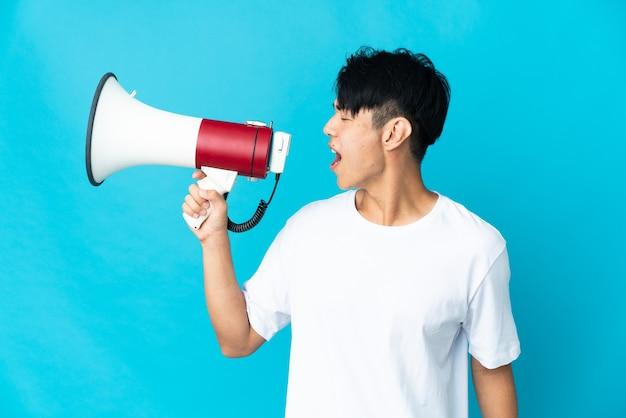 Jeune homme chinois isolé sur mur bleu criant à travers un mégaphone pour annoncer quelque chose en position latérale