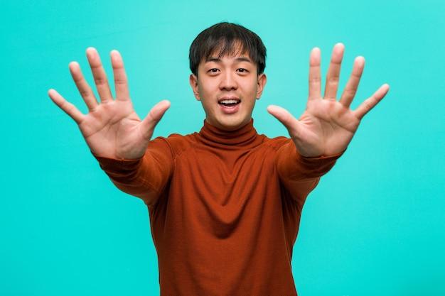 Jeune homme chinois montrant le numéro dix
