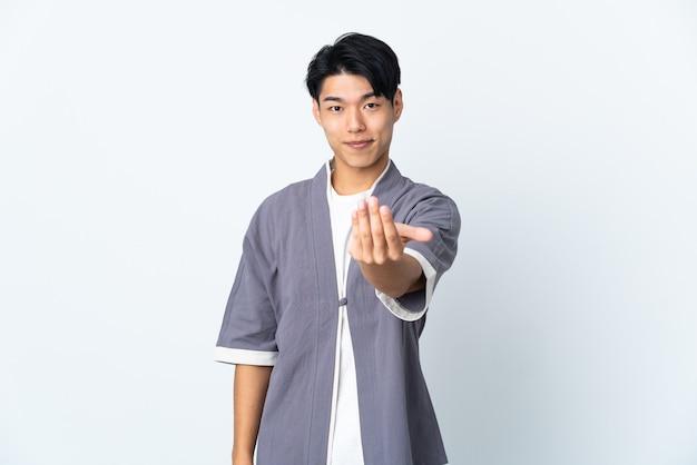 Jeune homme chinois sur un mur isolé invitant à venir avec la main. heureux que tu sois venu