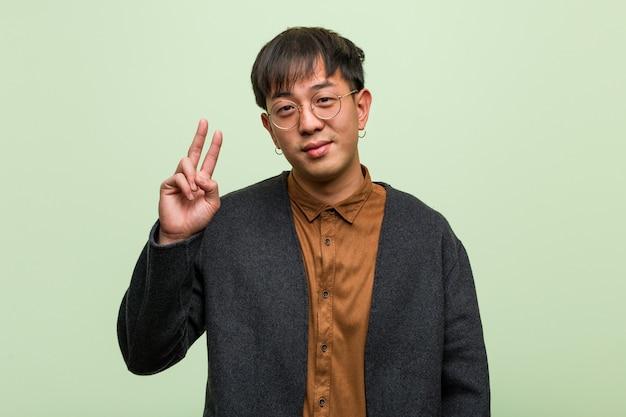 Jeune homme chinois portant un style de vêtements cool sur un fond vert