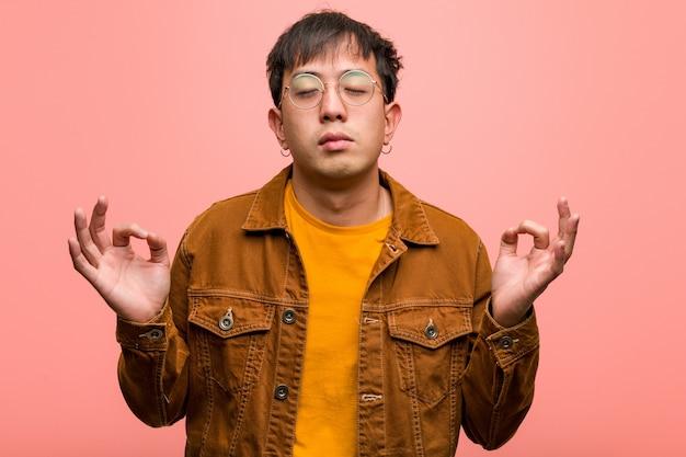 Jeune homme chinois portant une veste effectuant le yoga