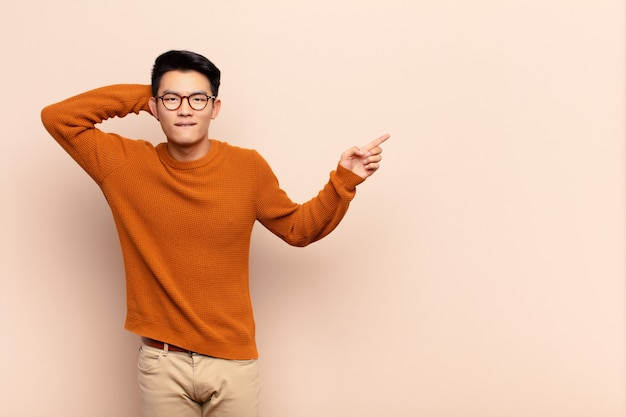 Jeune homme chinois en riant, heureux, positif et surpris, réalisant une excellente idée en pointant vers l'espace de copie latérale contre un mur de couleur plat