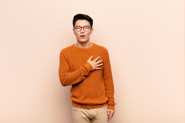 Jeune homme chinois se sentant choqué et surpris, souriant, prenant la main à cœur, heureux d'être l'un ou montrant sa gratitude contre le mur de couleur plat