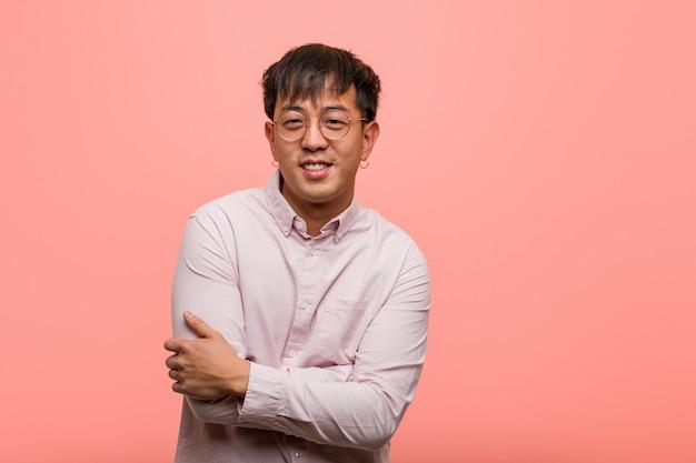 Jeune homme chinois souriant confiant et croisant les bras, levant les yeux