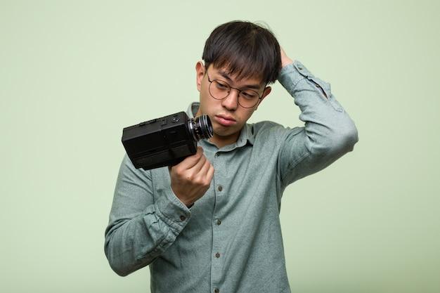 Jeune homme chinois tenant un appareil photo vintage inquiet et dépassé