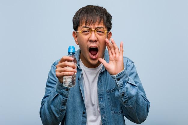 Jeune homme chinois tenant une bouteille d'eau criant quelque chose de joyeux à l'avant