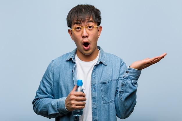 Jeune homme chinois tenant une bouteille d'eau tenant quelque chose sur la main de la paume