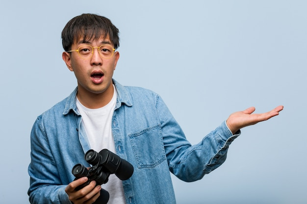 Jeune homme chinois tenant des jumelles tenant quelque chose sur la main de la paume