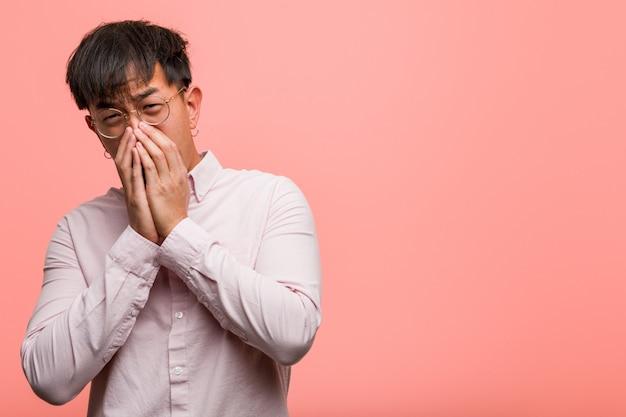 Jeune homme chinois très effrayé et effrayé caché