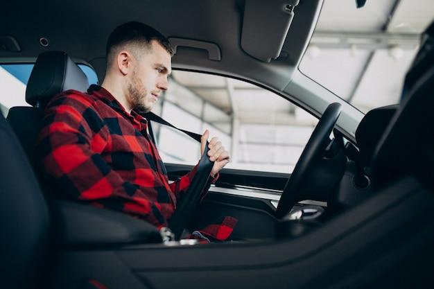 Jeune homme, choisir une voiture dans une salle d'exposition de voitures