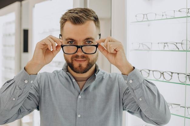 Jeune homme choisissant des lunettes au magasin d'optique
