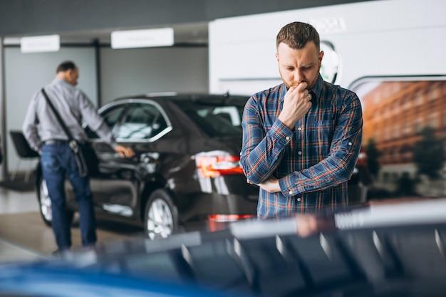 Jeune homme choisissant une voiture dans une salle d'exposition