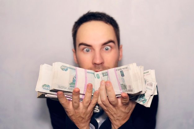 Un jeune homme choqué détient un million de roubles en billets de mille dollars. gagner à la loterie. le bénéfice de l'entreprise.