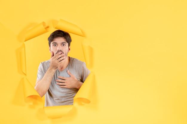 Jeune homme choqué sur fond de papier jaune déchiré beau mec intérieur du visage