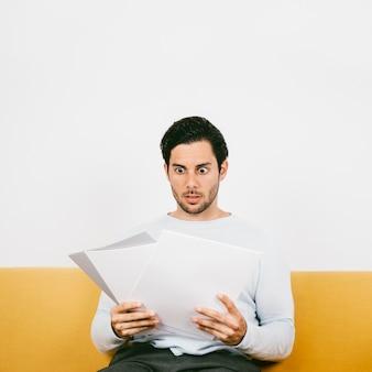 Un jeune homme choqué vérifiant les papiers