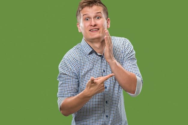 Le jeune homme chuchotant un secret derrière sa main sur fond vert