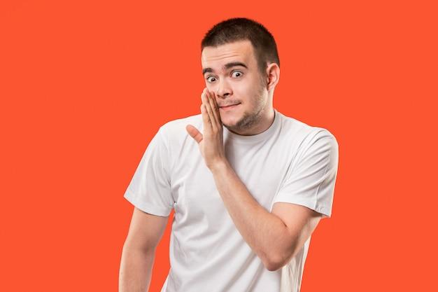 Le jeune homme chuchote un secret derrière sa main sur orange