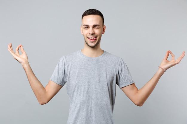 Jeune homme clignotant drôle dans des vêtements décontractés montrant la langue se tenant la main dans un geste de yoga relaxant en méditant