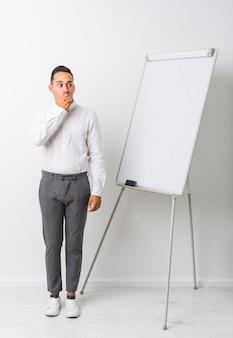 Jeune homme de coaching latin avec un tableau blanc réfléchi à la recherche d'un espace vide couvrant la bouche avec la main.