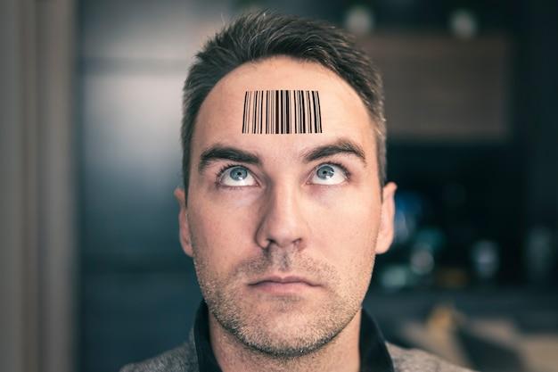 Jeune homme avec un code qr sur son front. un homme avec une expression stupide regarde son code qr sur sa tête. le concept de déchiqueter la population. contrôle et gouvernance mondiaux