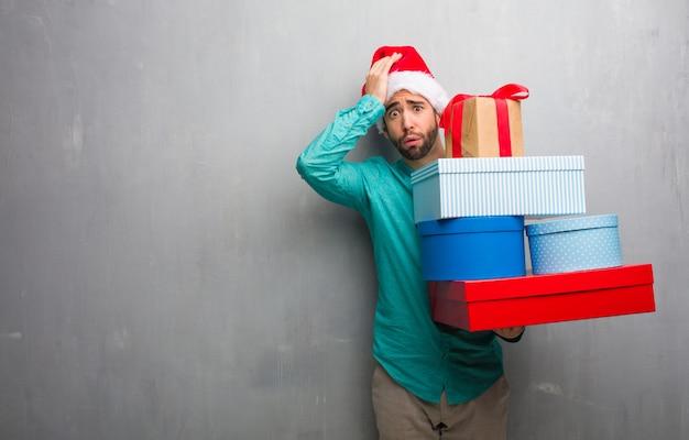 Jeune homme coiffé d'un chapeau de père noël avec des cadeaux inquiets et dépassés