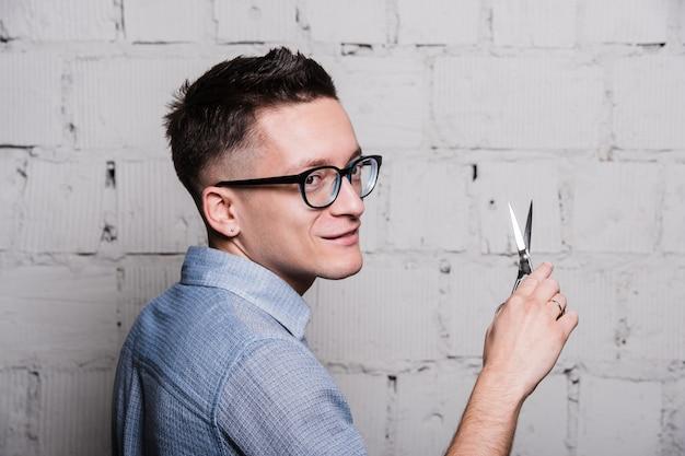 Jeune homme coiffeur dans des verres, posant avec des ciseaux, sur le mur de briques grises